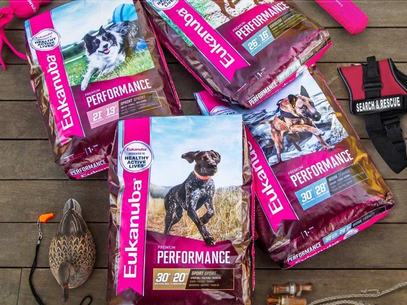 bags of Eukanuba Premium Performance Line dog food on a wooden floor.