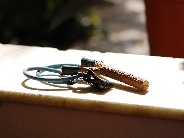 A slingshot on a windowsill in the sun.