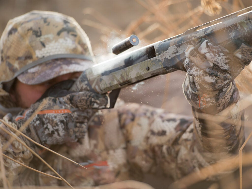 A hunter in full camo fires a shotgun in heavy brush.