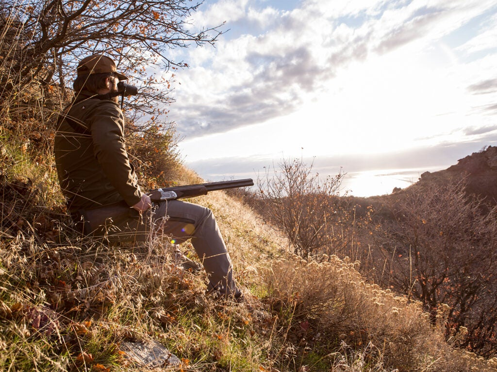 A hunter sits on a hillside with a shotgun in his laugh while he's glancing through binoculars.