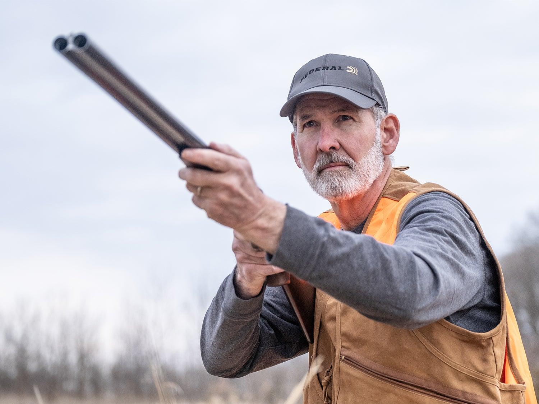 An older man in a vest and long sleeve shirt aims a shotgun in an open field.