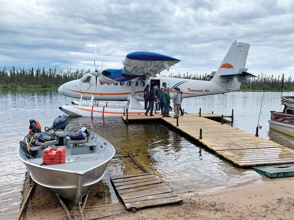 A large floatplane at the docks of a fishing camp next to an aluminum outboard boat.