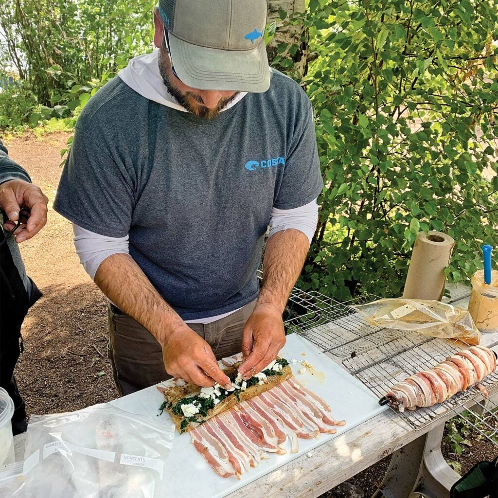 A bearded man wearing a hat prepares northern pike meat with toppings before wrapping the fillings in strips of bacon.