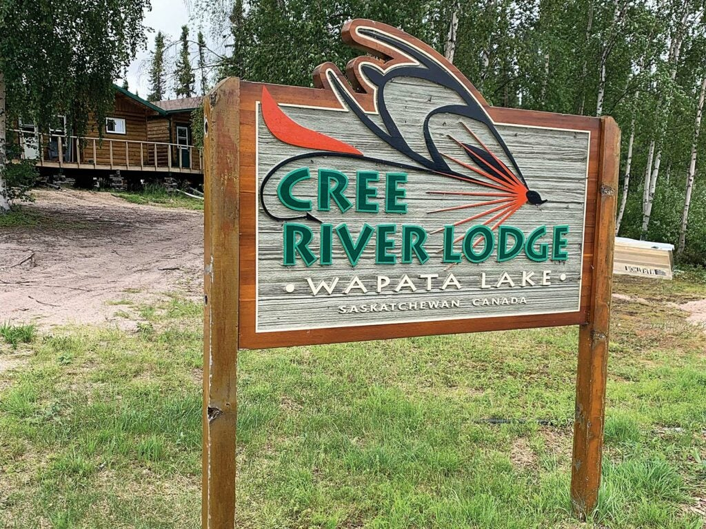 A wooden painted sign with the words: Cree River Lodge at Wapata Lake