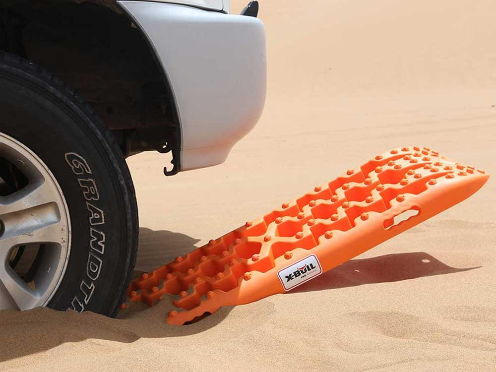 Traction board with SUV in sand.
