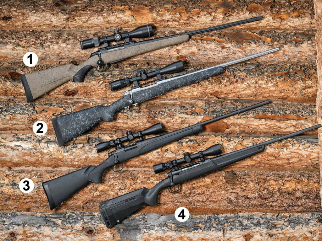 Four rifles arranged on a wooden table.