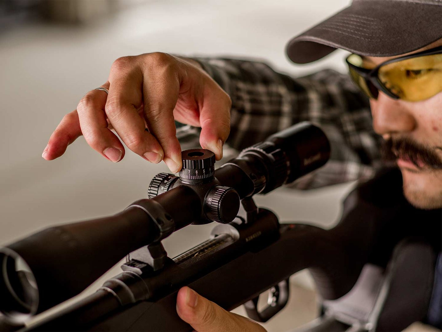 A man in shooting safety goggles adjusting a riflescope.