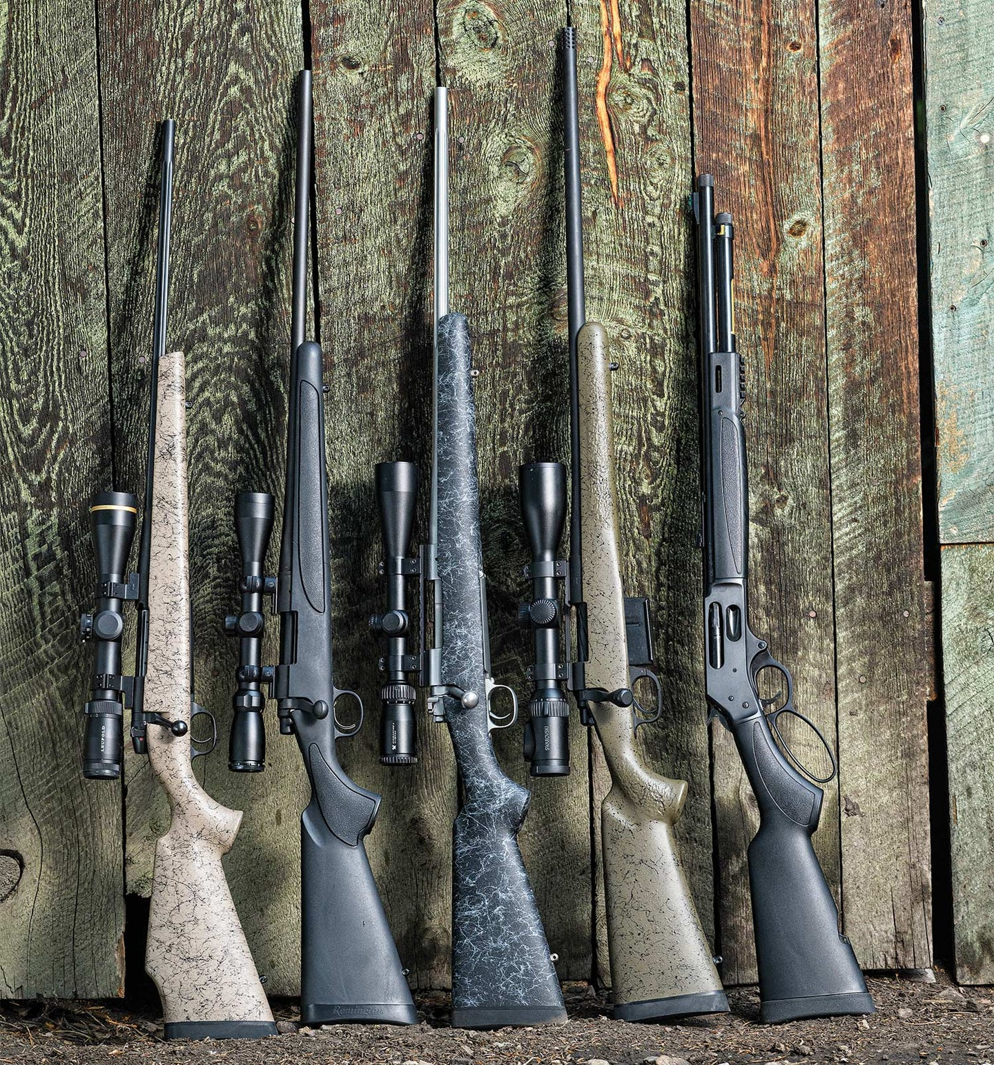Five rifles lined up and leaning against a wooden wall.