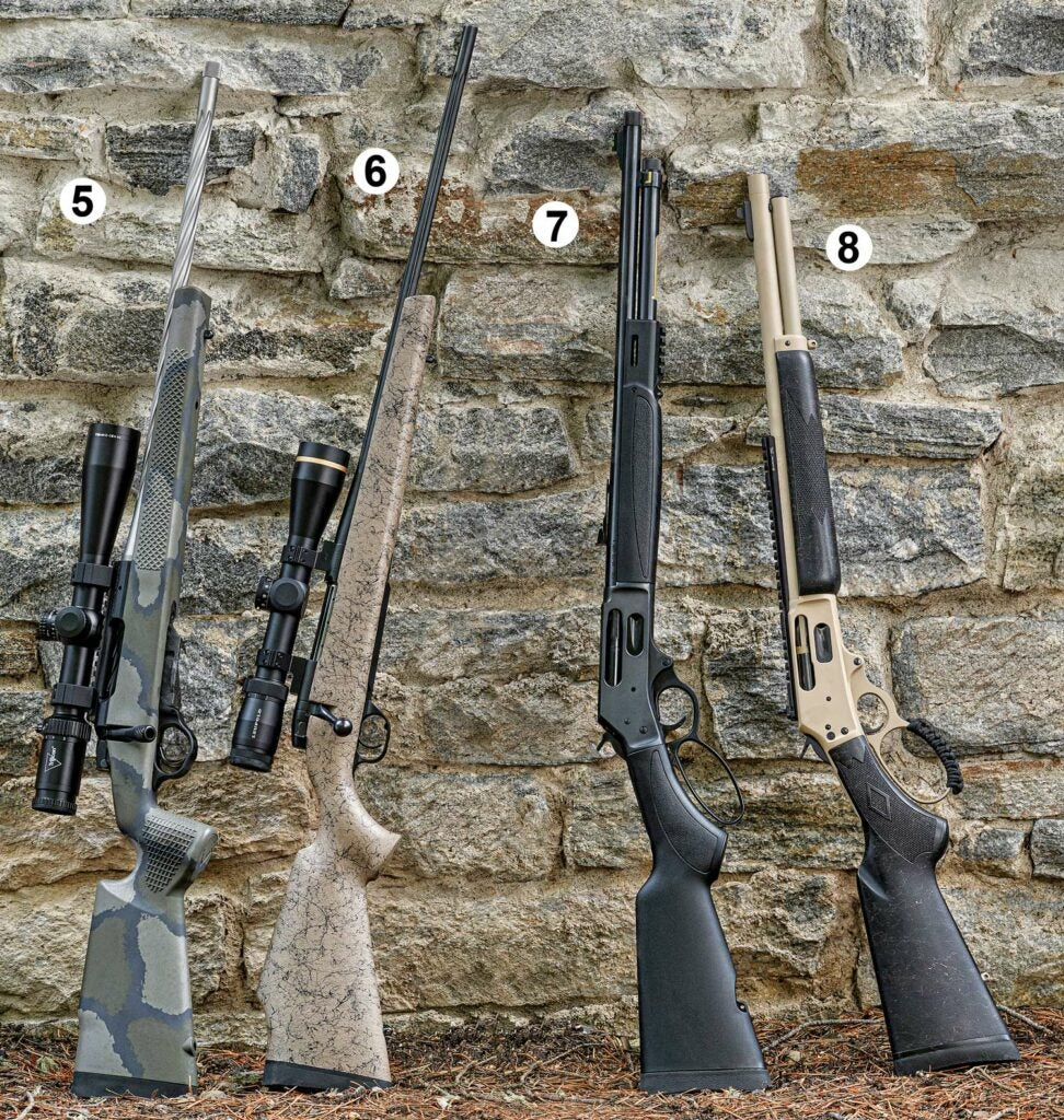 Four rifles leaning against a stone wall.