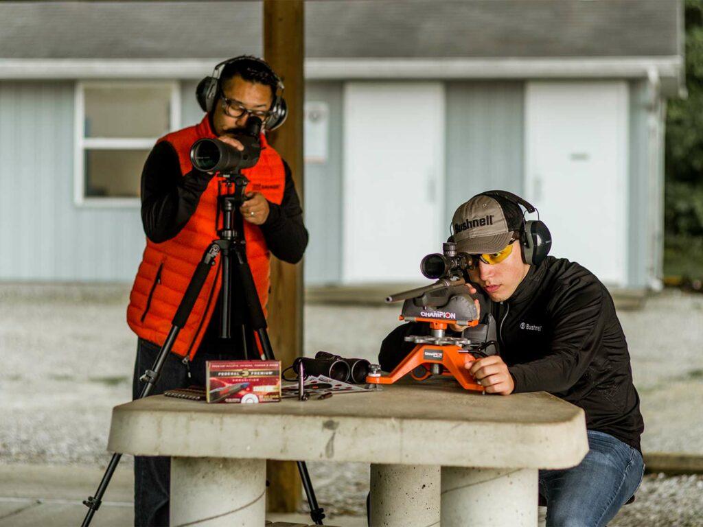 Two men adjusting riflescopes and making adjustments at a shooting range.