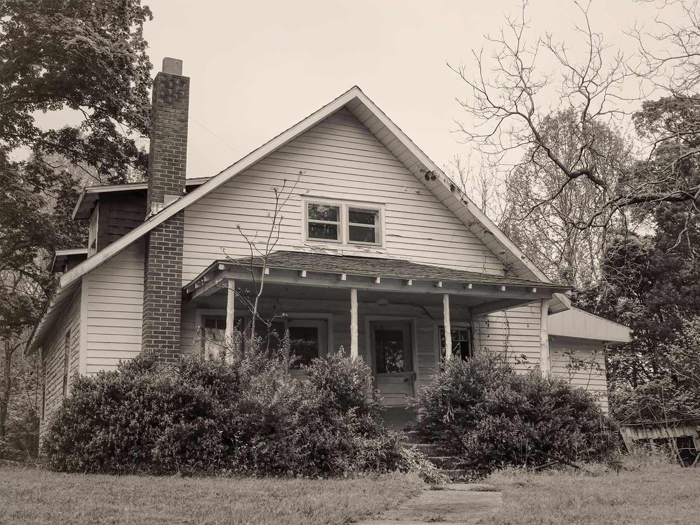 A black and white photo of an old farm house with peeling paint and oversized bushes growing beside the front porch.