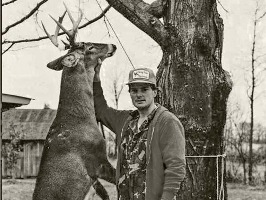 A black and white photo of a man standing next to a deer hanging from a tree branch.