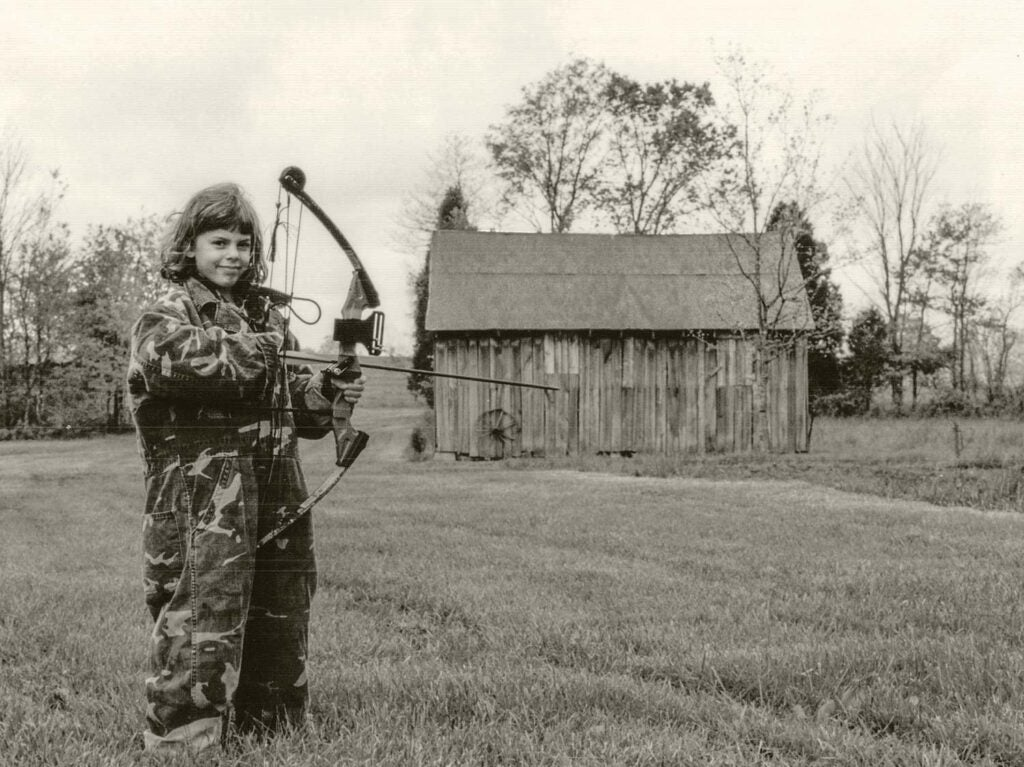 A black and white photograph of a young girl in oversized camoflauge coveralls while holding a large compound bow in front of old farm buildings.