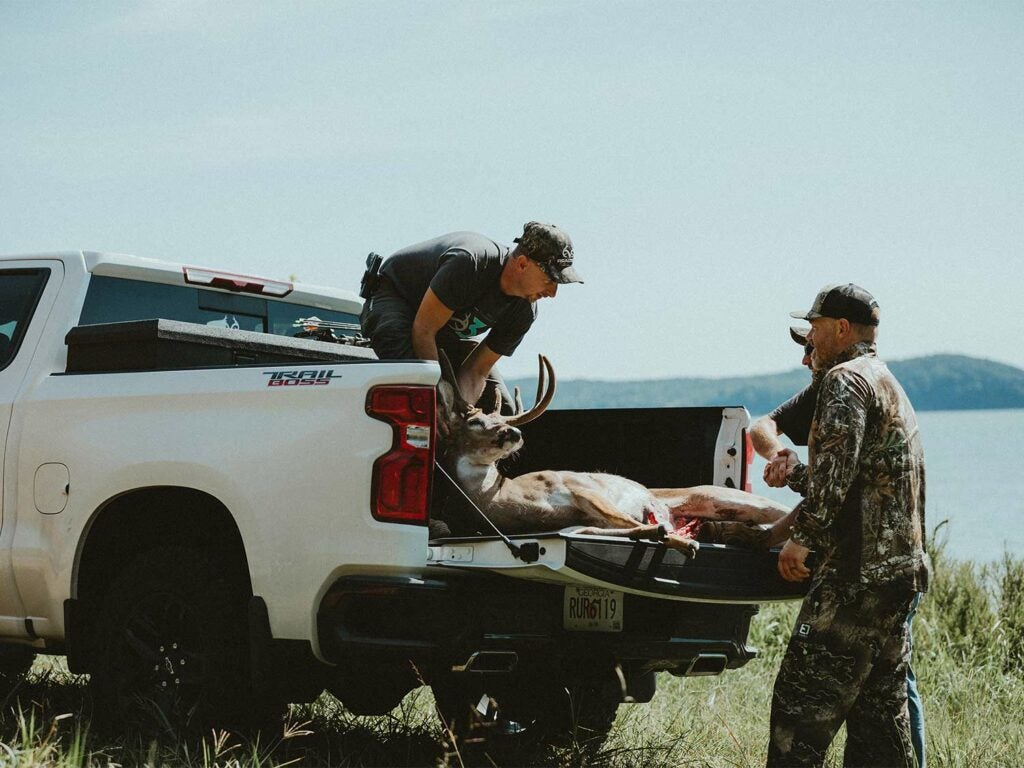 Two hunters pull a large whitetail buck into the bed of a truck.