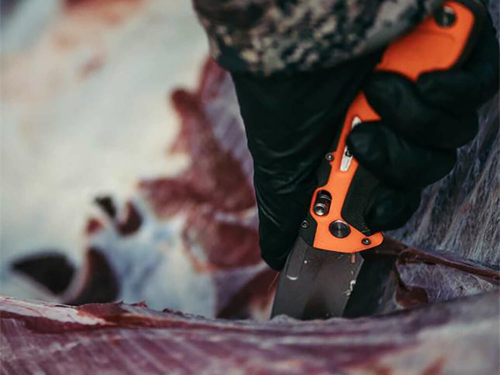 A hand pulling a knife through wild game meat to separate the skin from the meat.