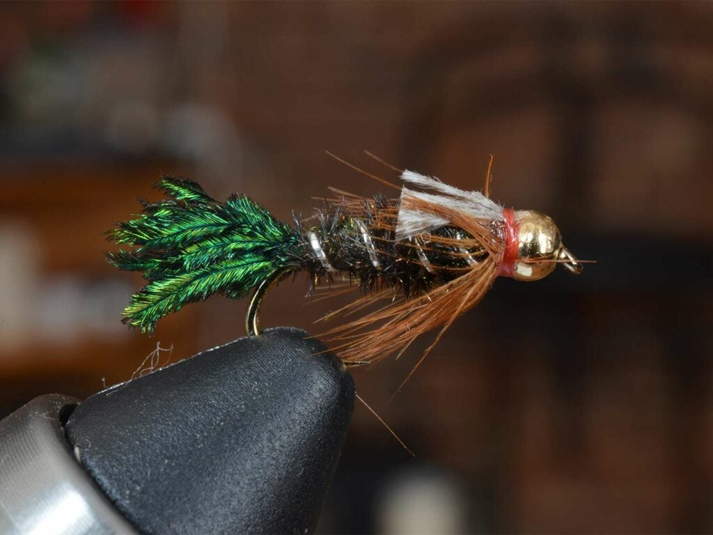 A green, copper and silver fly lure secured in a vice grip.