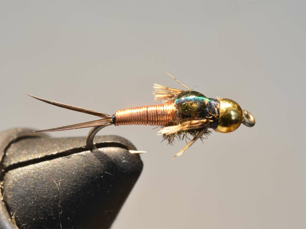 A copper, gold and green fly lure held in a vice.