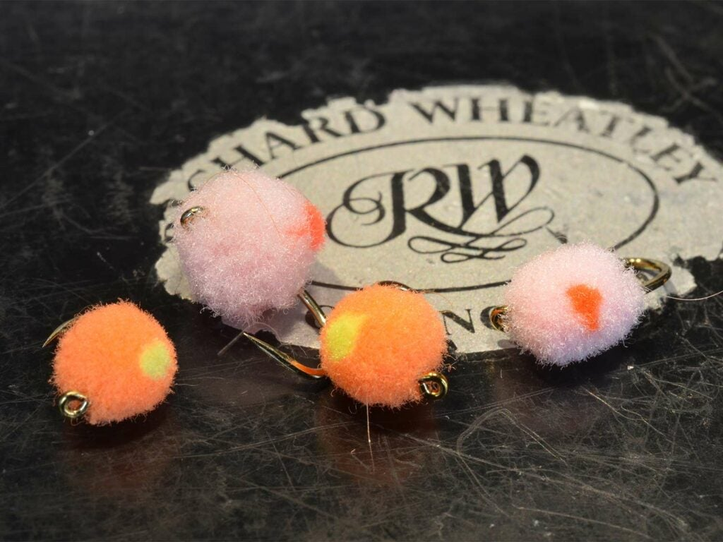 Four fuzzy fly lures mimicking the shape and color of salmon egg patterns.