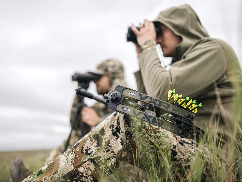 Two hunters scouting a mountainside through binoculars.