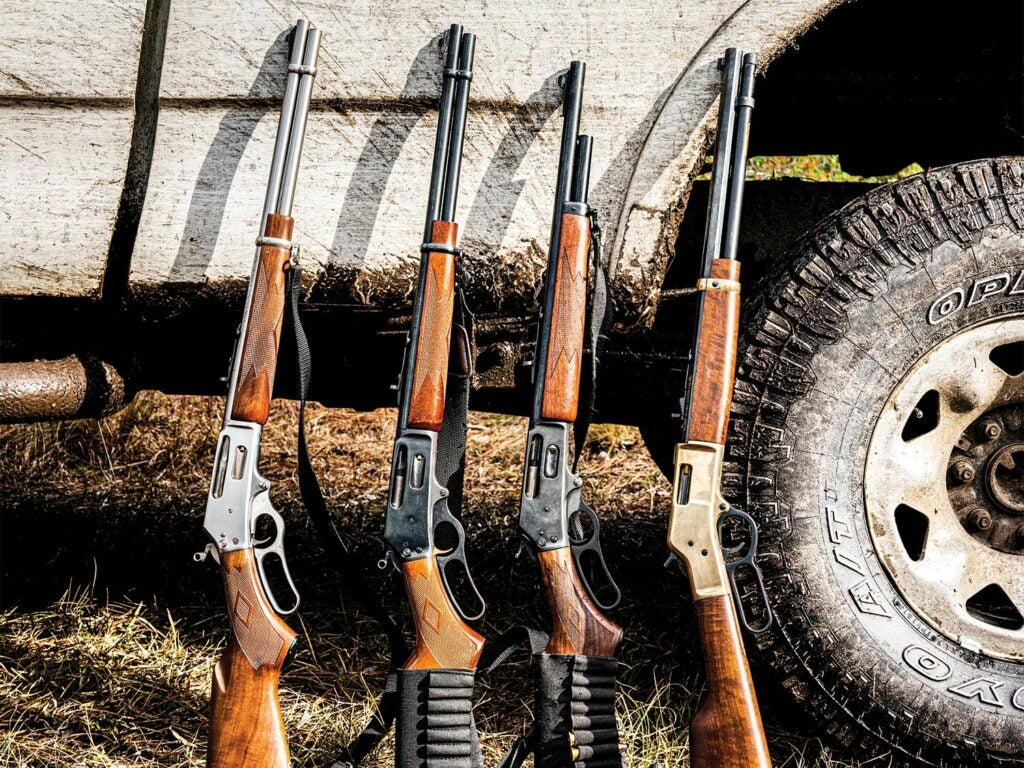 A lineup of four lever-action rifles leaning against a muddy pickup truck.