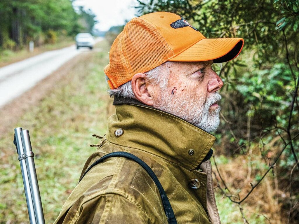 A man with a rifle slung over his shoulder and wearing an orange hunting cap looks into the treeline next to a road.