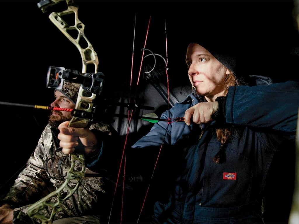 A female hunter draws back on a compound bow.
