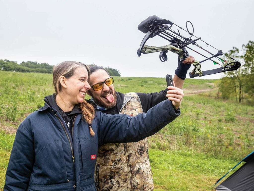 A man and woman stands in an open field while taking a selfie.