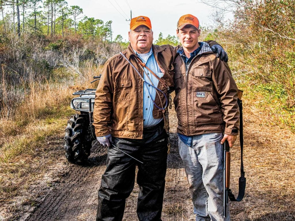Two hunters wearing orange caps stand in a muddy trail in front of a four-wheeled ATV.