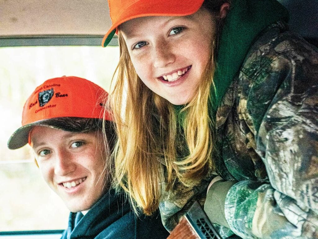 Two children, a bow and a girl, face the camera and smile while wearing hunting gear.