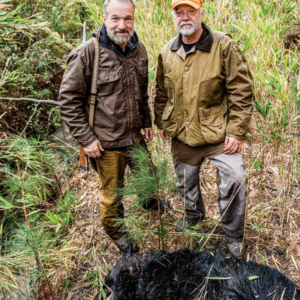 Two hunters stand behind a dead black bear and smile at the camera.