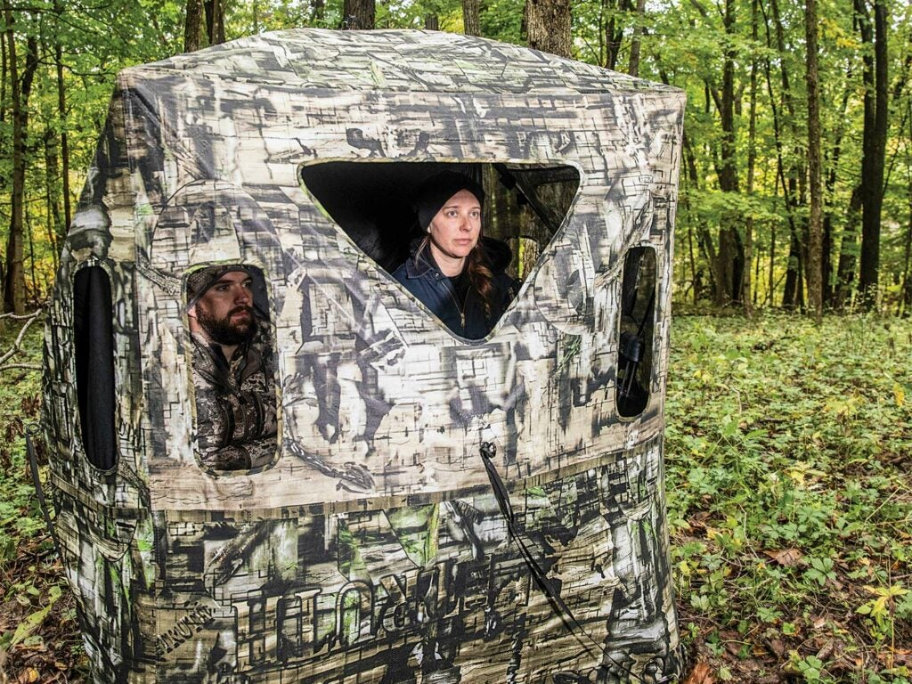 A woman and man hunter bunker down in a hunting blind in the woods.