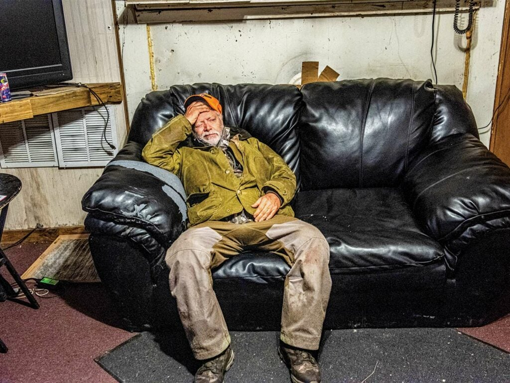 A tired male hunter relaxes on a black leather couch in a hunting cap.