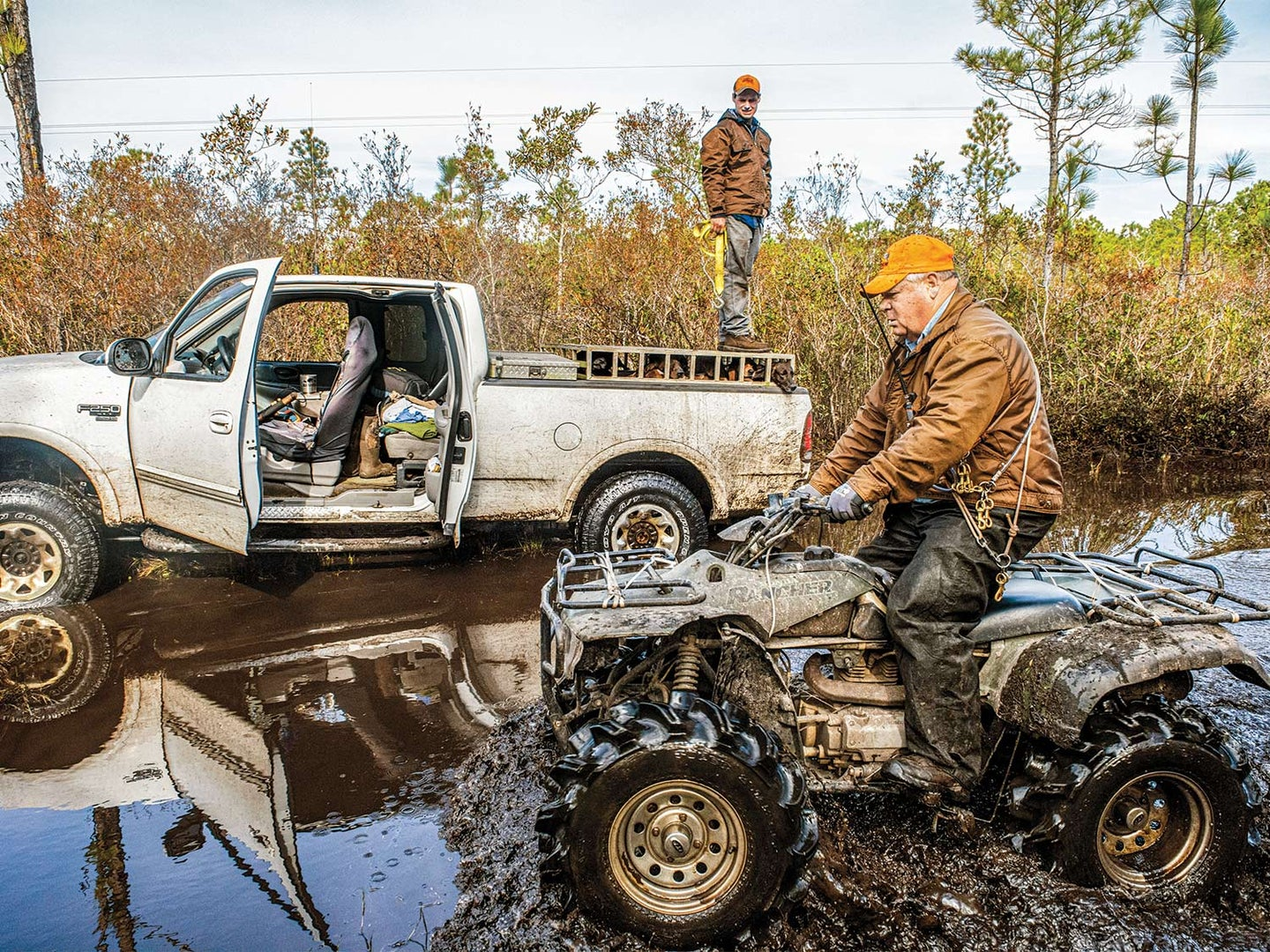 A hunter drives a four-wheeled ATV through the muddy water while one stands on top of a dog cage in the bed of a truck in the muddy water.