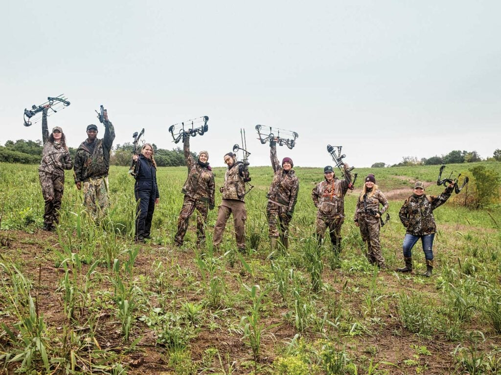 A group of nine hunters hold up their compound bows in celebration while standing in a large open field