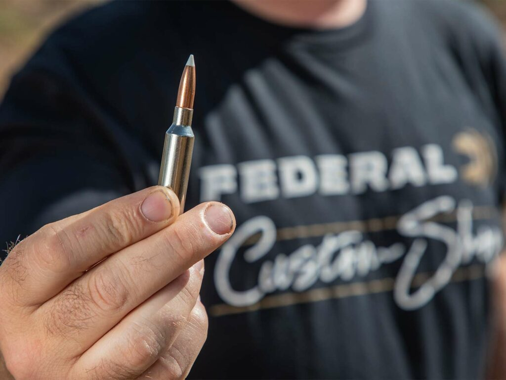 A man wearing a Federal custom shop shirt holds a custom ammo round in his hand.