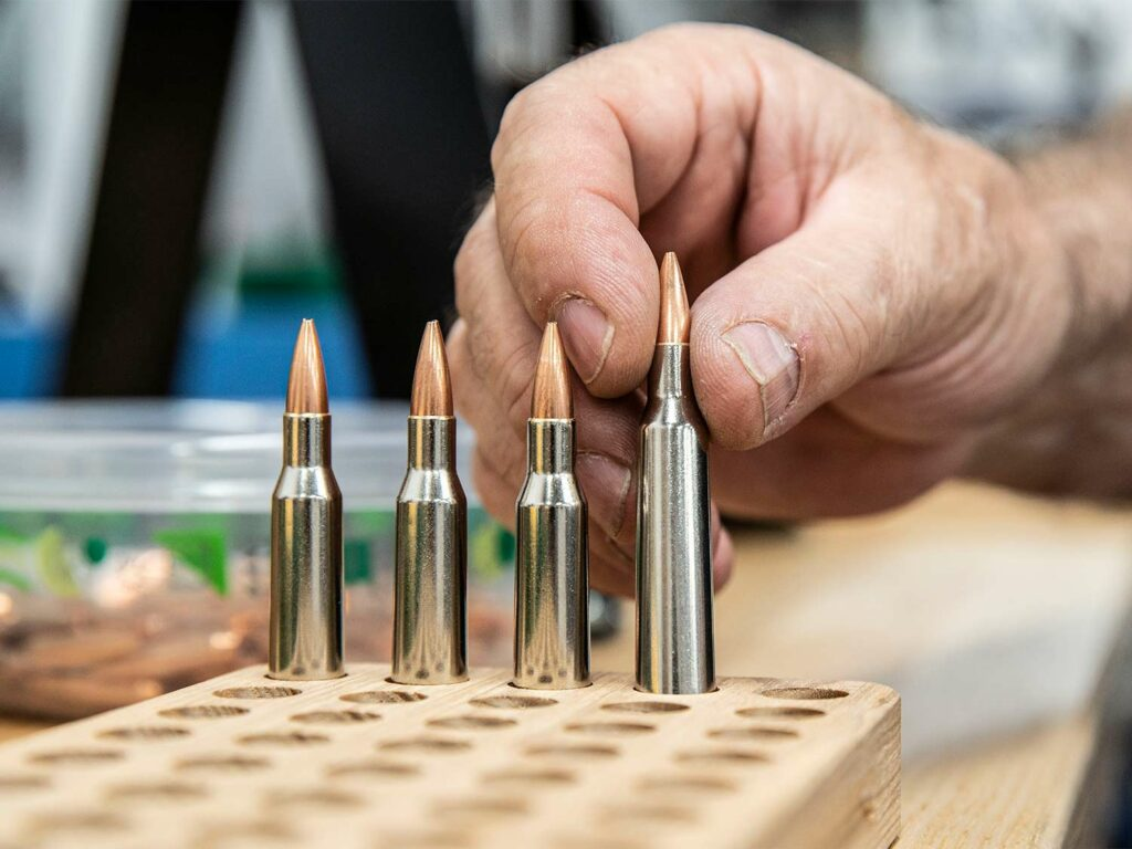 A hand places custom bullets into a wooden plank with holes drilled into it.