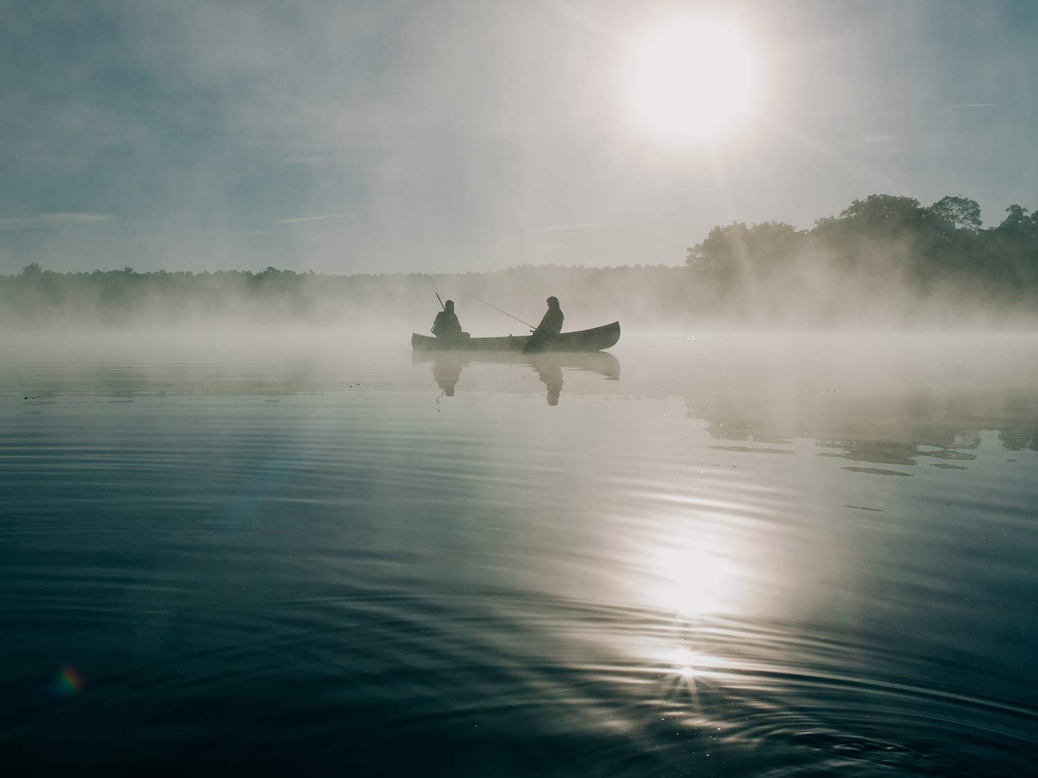 Two anglers sit and fish on a canoe in the middle of a morning sunrise, with fog rising off the smooth surface of the lake.