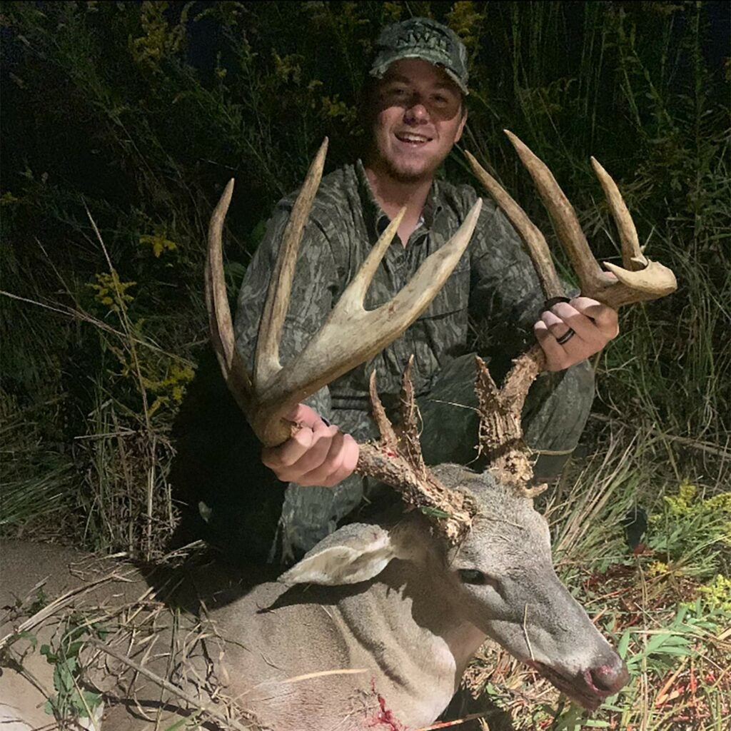 A hunter holds a dead whitetail deer's head by the antlers.