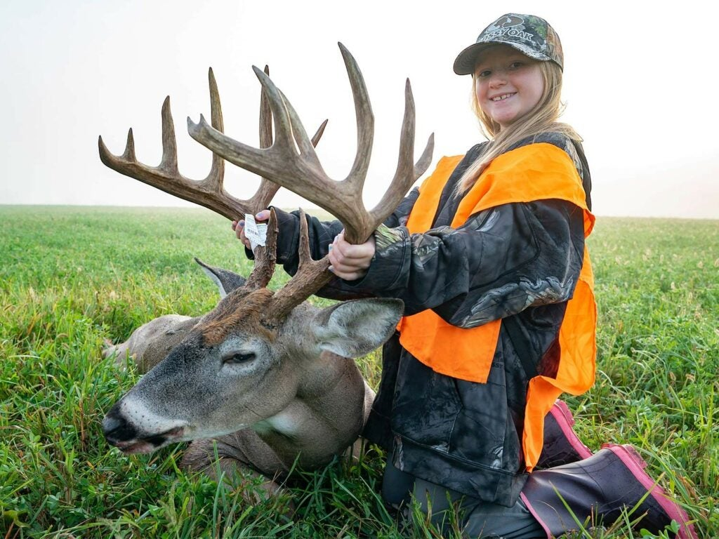 A young girl holds up a whitetail deer's head by the antlers.