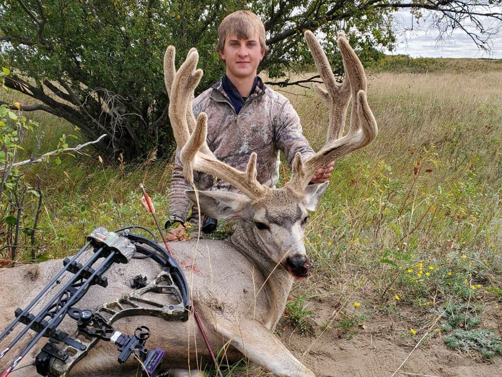 A young man kneels behind a mule deer and holds up its head by the antlers.