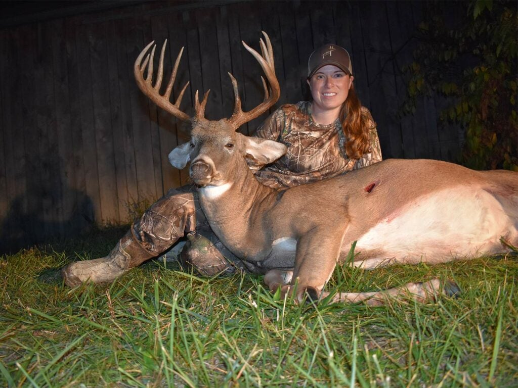 A woman hunter in full camo sits behind a dead whitetail buck at night.