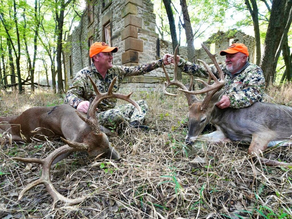 Two men kneel behind two whitetail deer and bump their fists together.