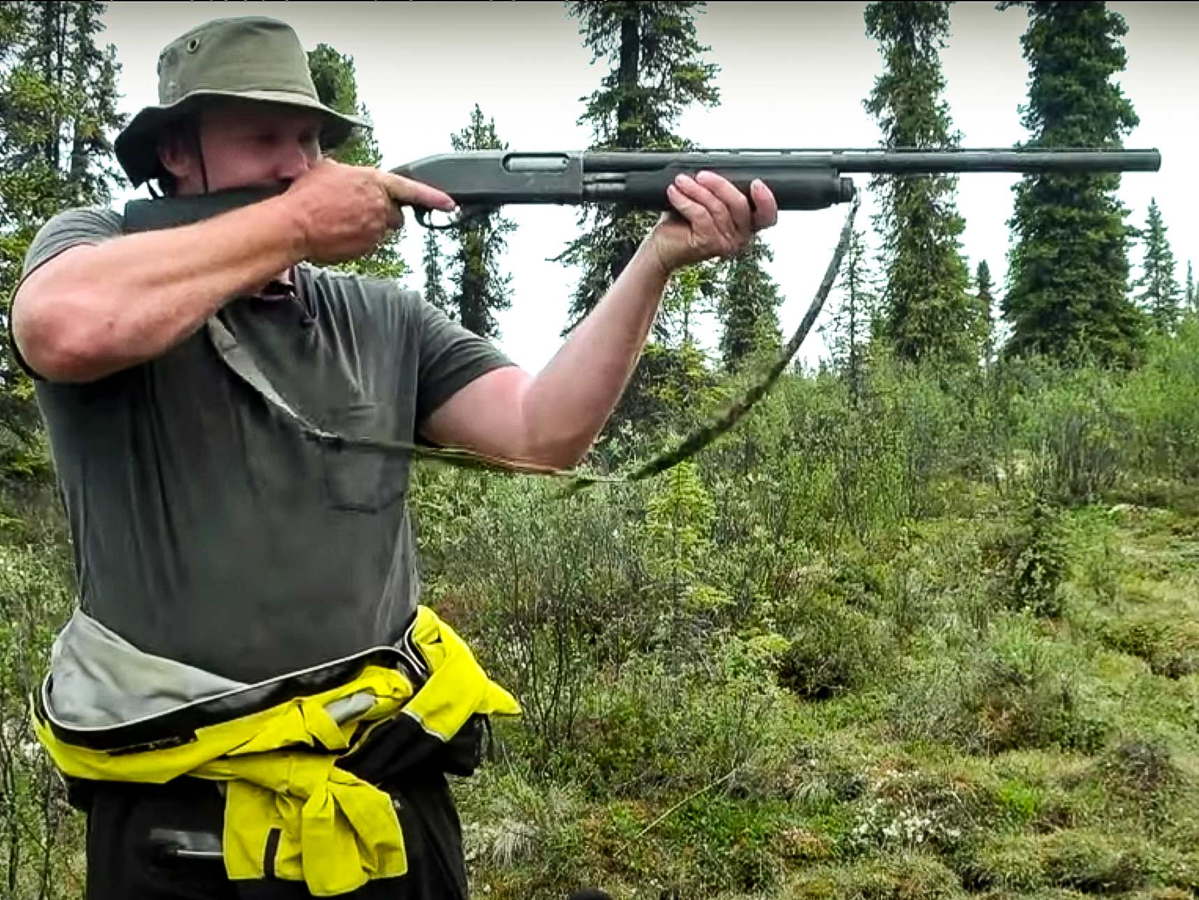 A man holds a shotgun to his shoulder in a lush green forest clearing.