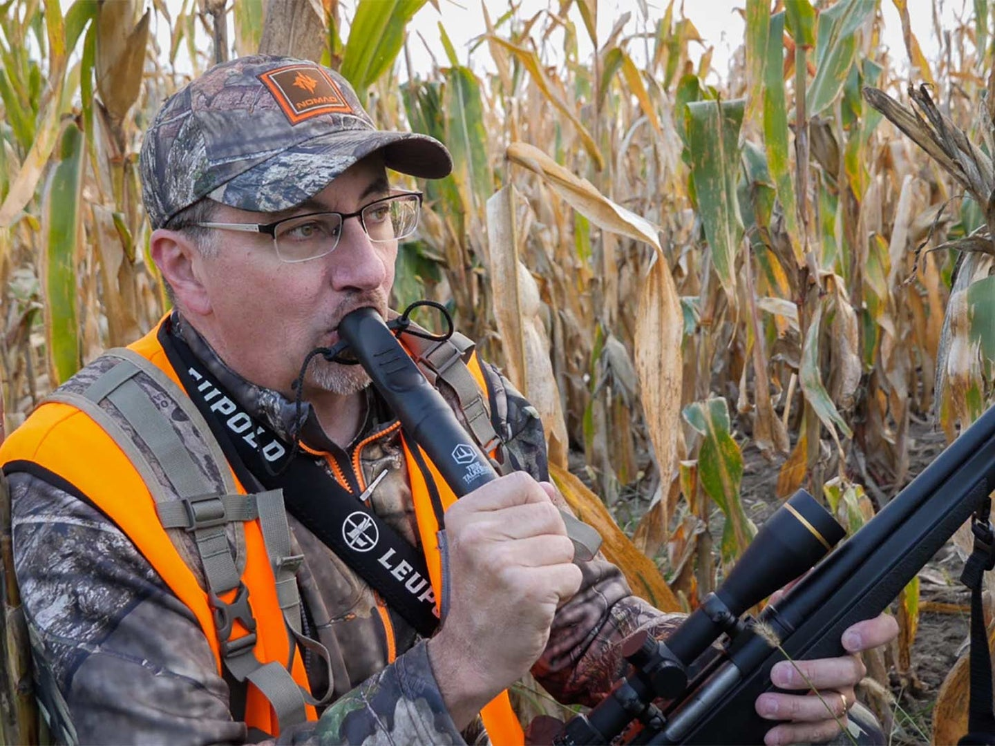 A hunter in camo and orange vest holds a rifle in one hand while blowing into a deer hunting grunt call held in the other.