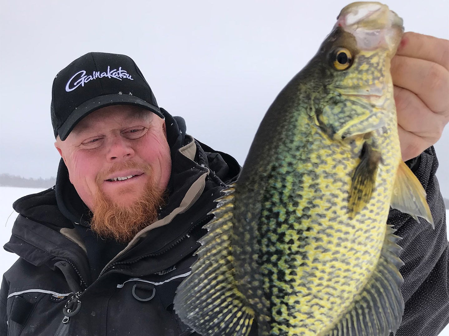 A man in cold-weather gear holds up a fish caught from the ice.