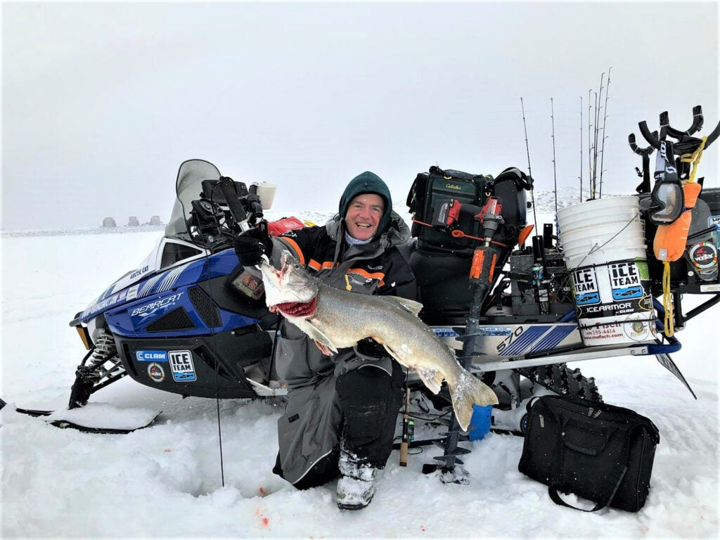 A man holds up a large fish pulled from ice fishing and is surrounded by fishing gear.
