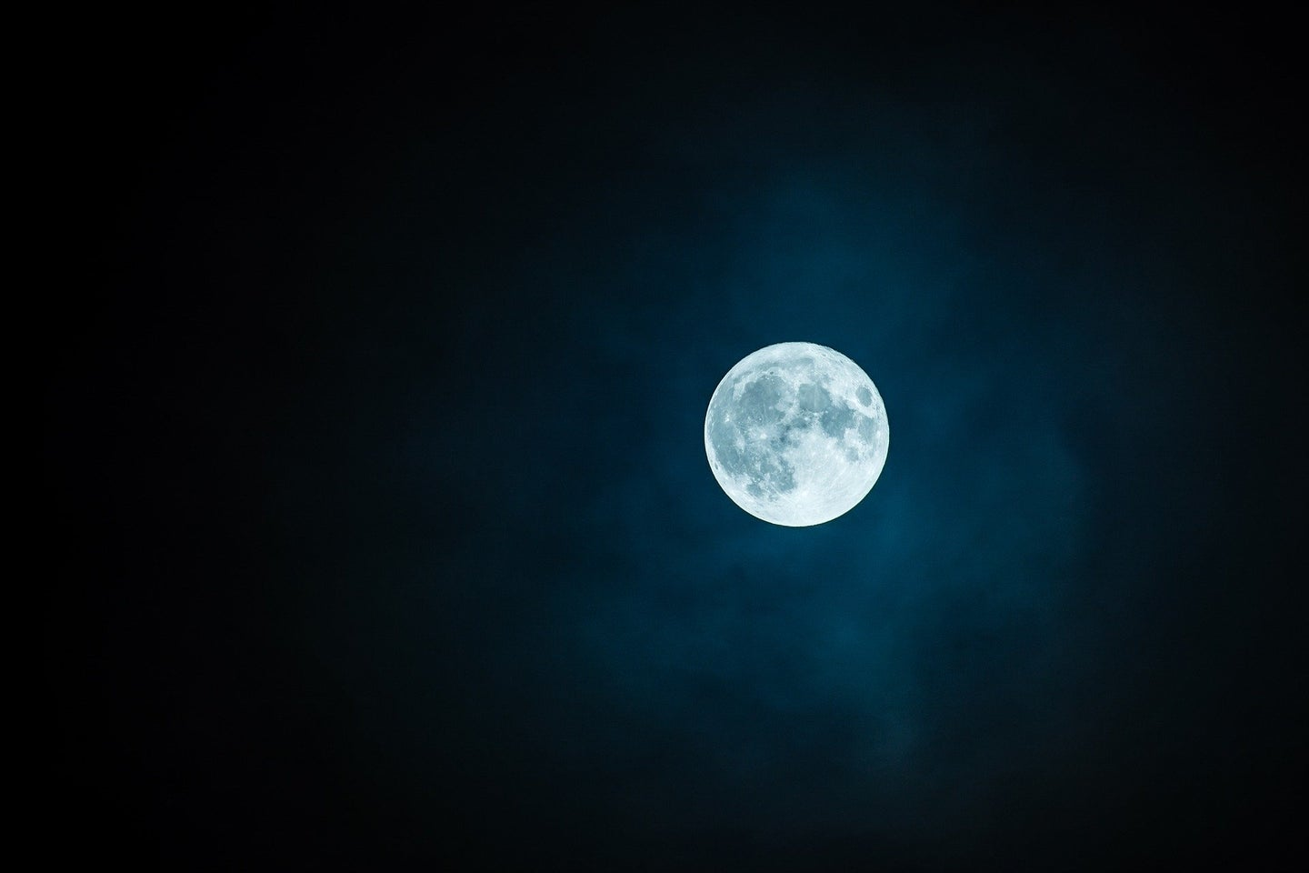 A full moon in the night sky with no stars.