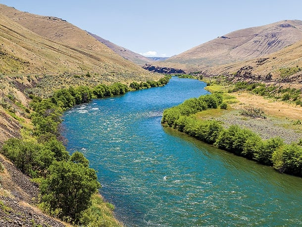 The lower Deschutes River flows through central Oregon. Lush greenery and rolling hills lines its banks.