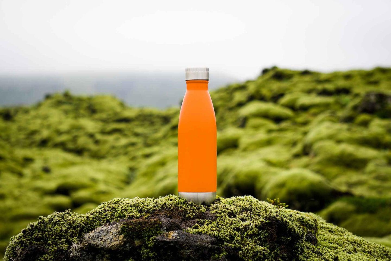 Orange water bottle on a mountain top