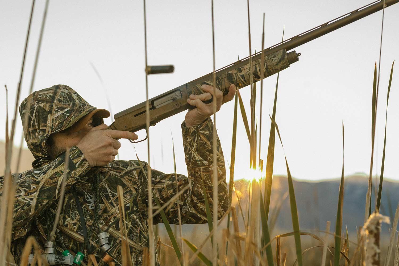A hunter with a shotgun aims it into the air.